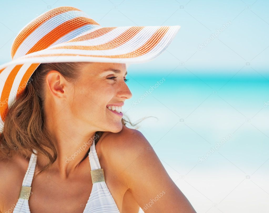 Portrait of happy young woman in swimsuit and beach hat looking