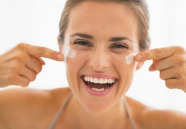 Happy young woman having fun time while applying cream in bathroom