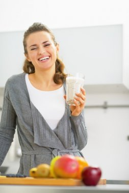 Happy young woman drinking smoothie in kitchen