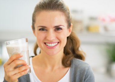 Portrait of happy young woman drinking smoothie in kitchen