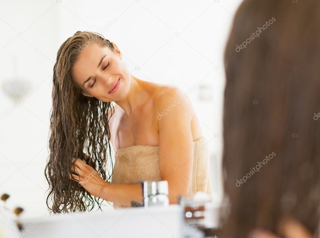 Happy young woman with wet hair in bathroom