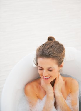 Portrait of happy young woman laying in bathtub