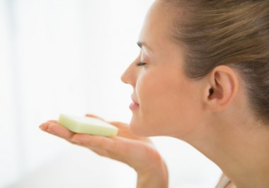 Woman smelling soap bar