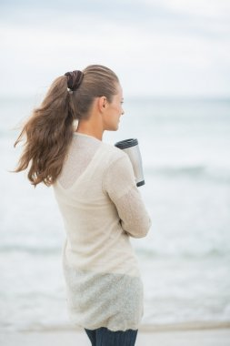 Woman on beach with hot beverage