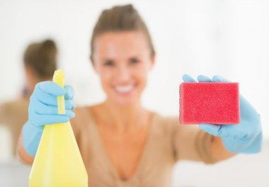 Housewife showing spray bottle and sponge