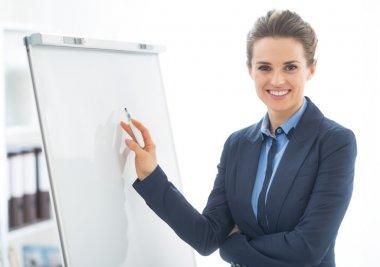 Happy business woman near flipchart