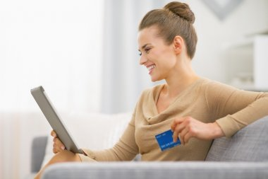 Happy woman with credit card using tablet pc