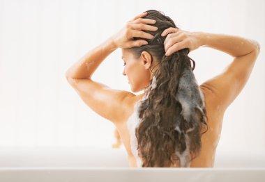 Young woman washing hair.