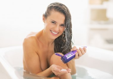 Smiling woman with hair conditioner in bathtub