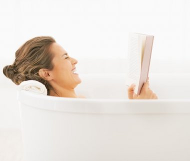 Smiling young woman in bathtub reading book
