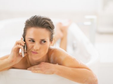 Concerned woman in bathtub talking cell phone