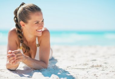 Happy young woman laying on beach