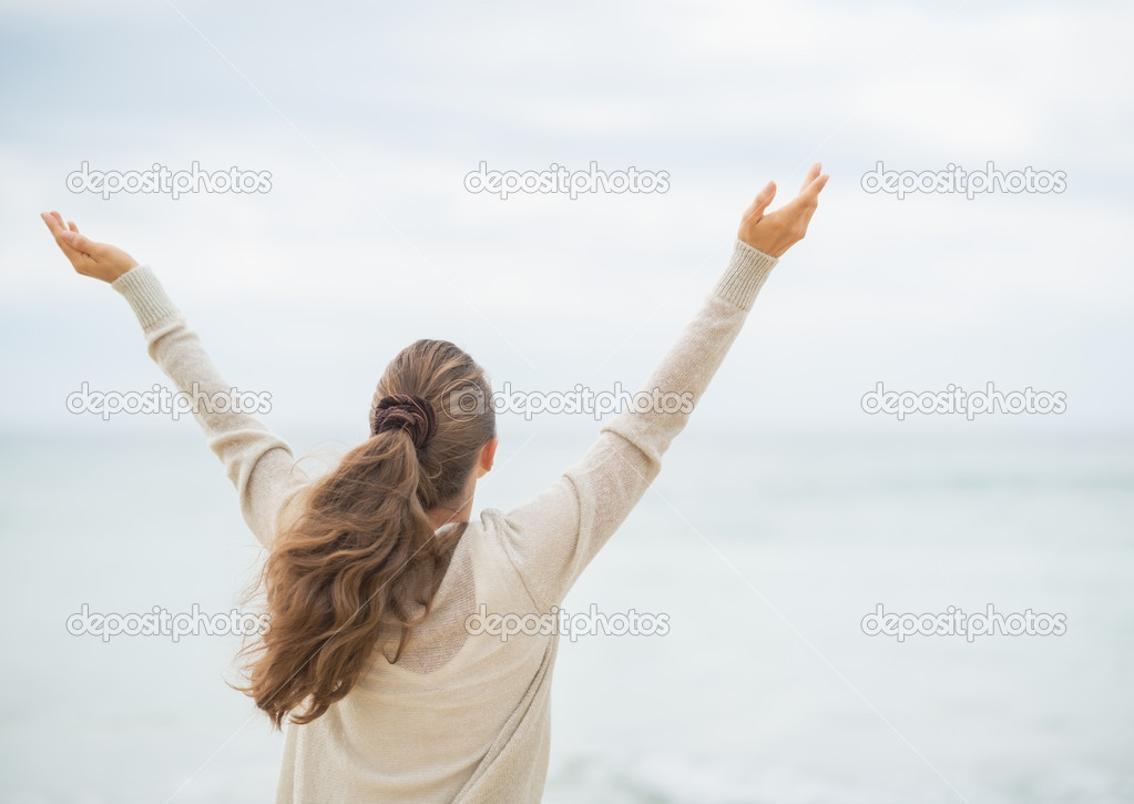 Woman on cold beach rejoicing success.