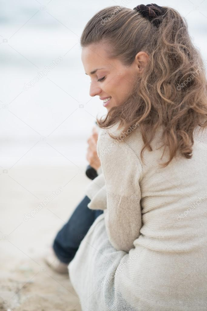 Happy woman sitting on cold beach