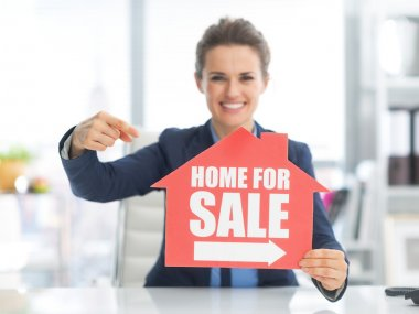 Realtor woman pointing on sign