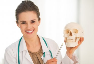 Doctor showing human skull