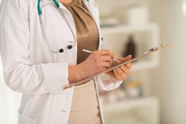 Doctor woman writing in clipboard