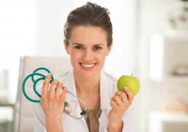 Happy medical doctor woman showing apple and stethoscope