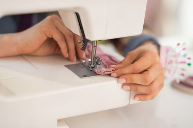 Closeup on seamstress sewing in studio