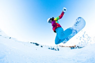 Girl snowboarder having great fun jumping