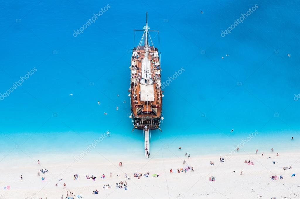 Grote zeil cruise schip verankerd op een wit zandstrand van boven