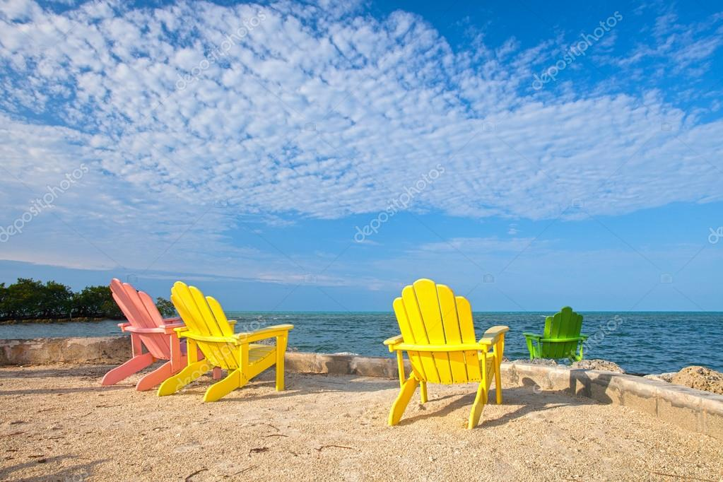 Summer scene with colorful lounge chairs at a tropical beach in Florida with blue sky and ocean