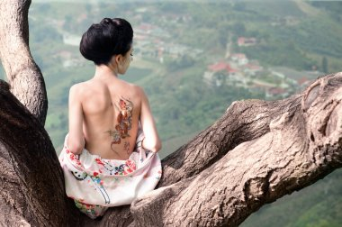 Woman with snake tattoo on her back on the tree branch (original)