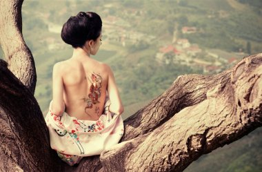 Woman with snake tattoo on her back on the tree branch