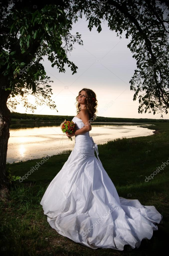 The bride at the riverside under the arch of branches, back view