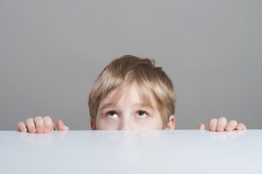 Boy looking up from behind the table