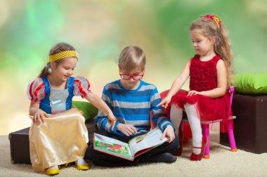 Boy reads a book to little girls