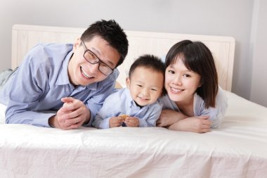 happy family lying on bed