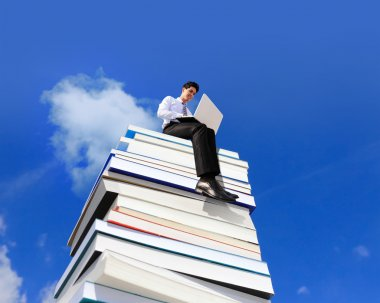 Happy business man using pc computer and sitting on a stack Of Books