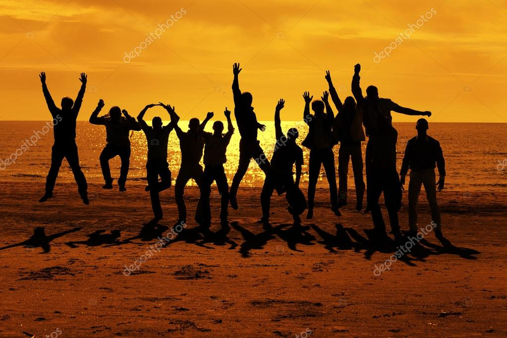Male friends are having fun and jumping up on the sunset