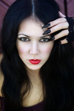 Closeup portrait of a beautiful gothic girl with red lips holding her hand with black sharp nails near the face