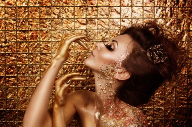 Attractive addicted hot brunette with beautiful golden makeup and gold caramel painted hands is posing in front of abstract golden background
