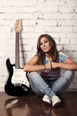 Young female musician is sitting on the floor near to her guitar