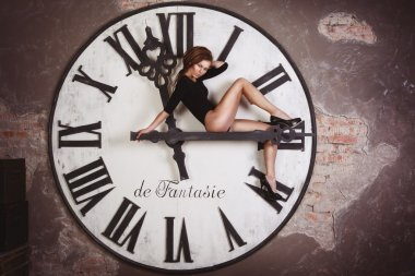 Sexy and attractive female is sitting on the giant clock arrows counting time