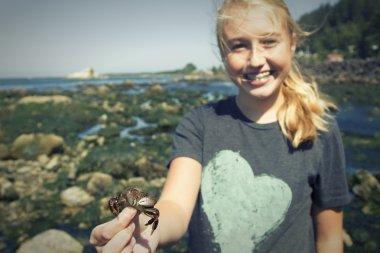 girl  holding a crab standing near tidal pools at Tillamook bay
