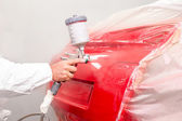 Auto painter spraying red paint on car in auto workshop