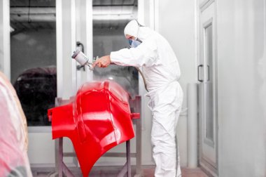 Auto worker spraying red paint on a front bumper of a car