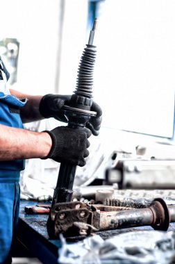 Auto engineer mechanic working on car shock absorber