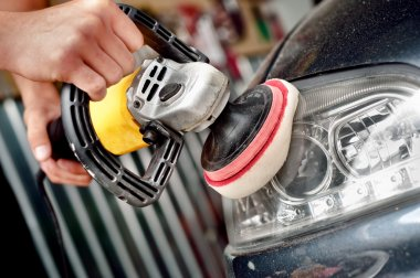 Car headlight cleaning with power buffer machine at service station