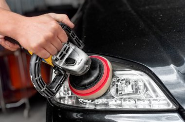 Car headlights cleaning with power buffer machine at car service