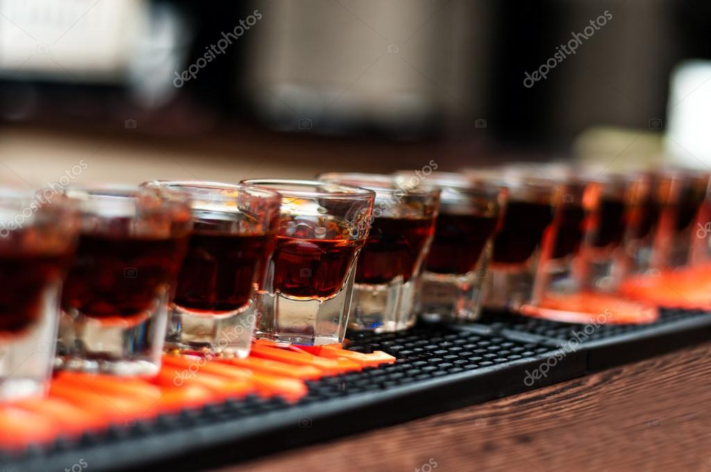 Red, strong alcoholic drink in small glasses on bar