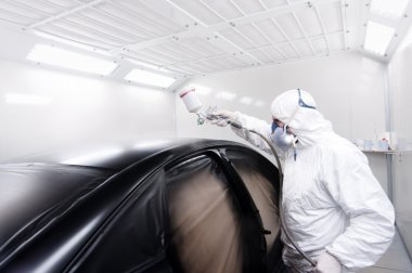Automotive mechanical engineer painting the body of a black car