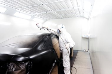 Automotive industry - engineer painting and working on a black body of a car and wearing protective gear