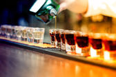 Bartender pouring strong alcoholic drink into small glasses on bar, shot glasses