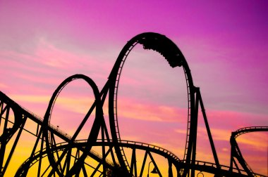Colorful silhouette of a roller coaster at sunset, after a sunny