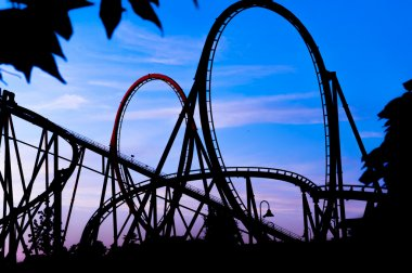 Silhouette of a roller coaster at a blue sunset during a fun fair at entartaiment thematic park